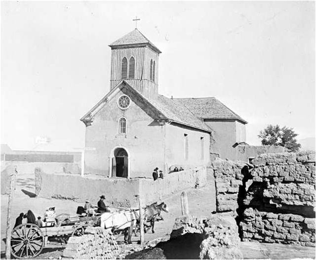 Old church with a horse drawn carriage and stone walls in front